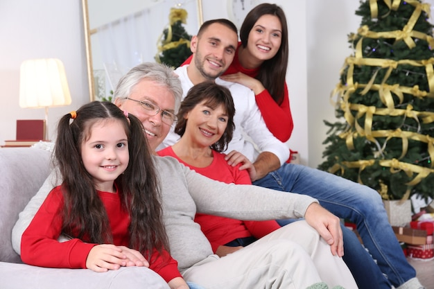 Szczęśliwa rodzina siedzi na kanapie w salonie udekorowanym na boże narodzenie