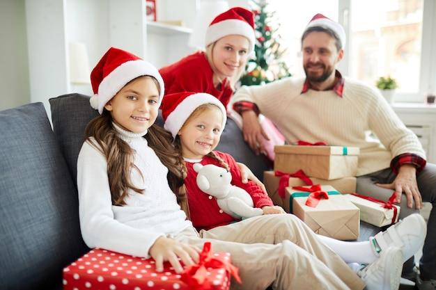 Szczęśliwa rodzina siedzi na kanapie z prezentami świątecznymi
