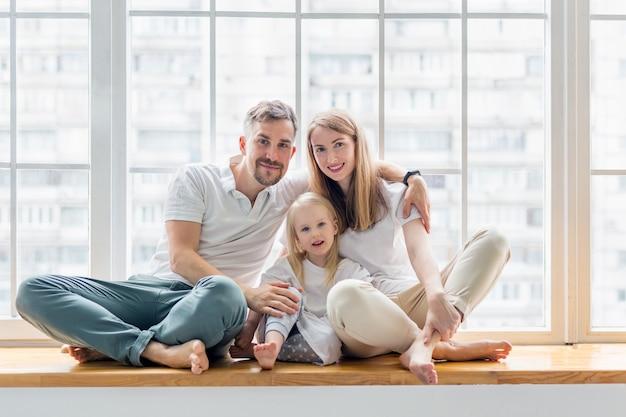Szczęśliwa rodzina siedzi na parapecie razem