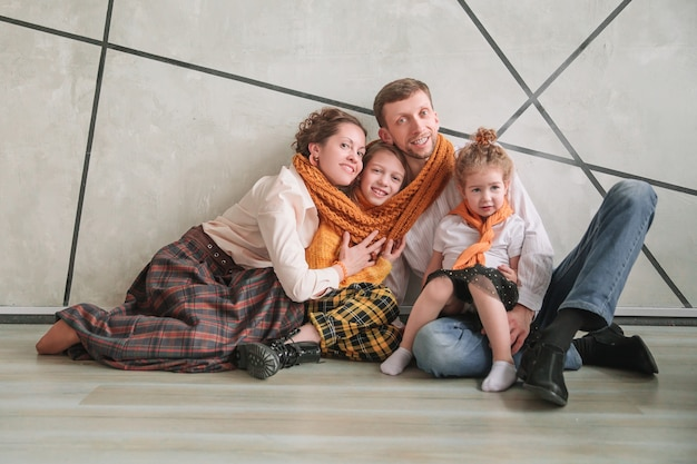 Szczęśliwa rodzina siedzi na podłodze w nowym mieszkaniu.