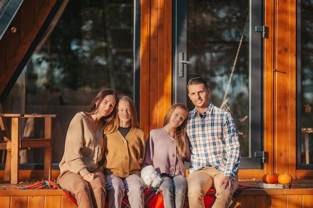 Szczęśliwa rodzina siedzi na tarasie swojego domu jesienią