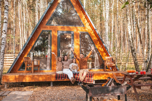 Szczęśliwa rodzina siedzi na tarasie swojego domu w jesienny dzień