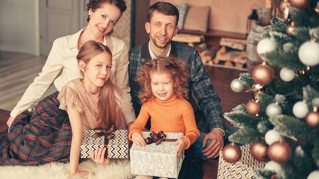 Szczęśliwa rodzina siedzi przy choince w przytulnym salonie. koncepcja wakacje