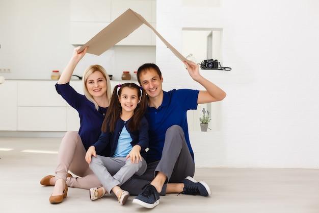 Szczęśliwa rodzina siedzi razem i robi znak domu