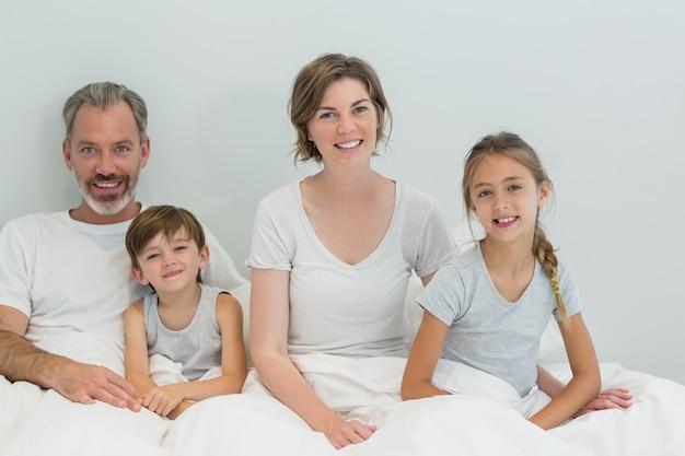 Szczęśliwa rodzina siedzi razem na łóżku w sypialni w domu