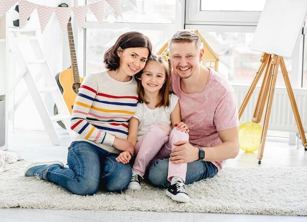 Szczęśliwa rodzina siedzi razem na podłodze w jasnym pokoju
