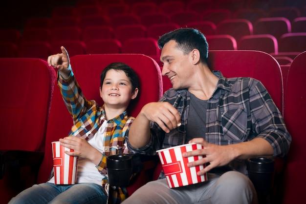 Szczęśliwa rodzina siedzi w kinie