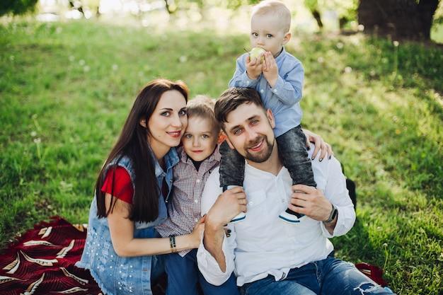 Szczęśliwa rodzina siedzi w parku wraz z dziećmi, obejmując
