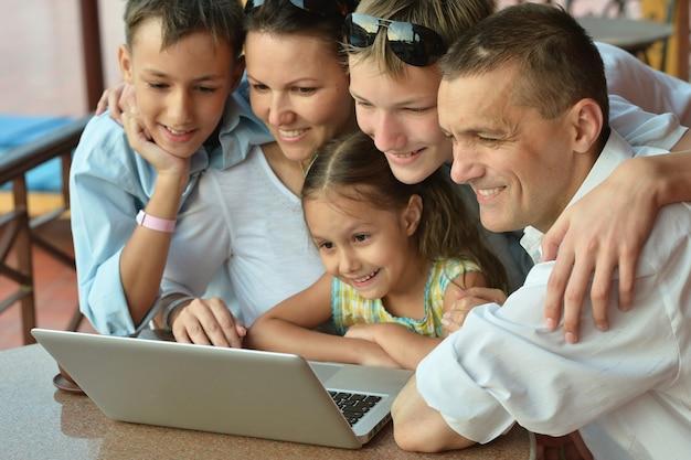 Szczęśliwa rodzina siedzi z laptopem na stole