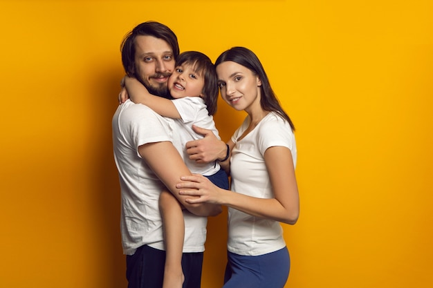 Szczęśliwa rodzina składająca się z trzech osób, chłopiec i dziecko w białych koszulkach stoją na żółtej ścianie