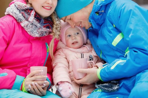Szczęśliwa rodzina składająca się z trzech osób przy filiżance gorącej herbaty w zimie na zewnątrz.