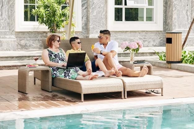 Szczęśliwa rodzina składająca się z trzech osób wypoczywa na szezlongach przy basenie