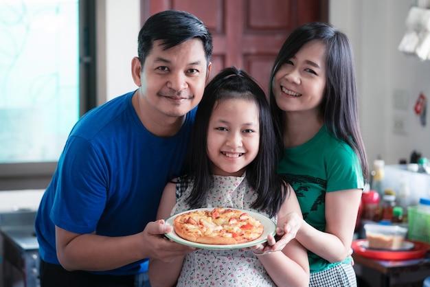 Szczęśliwa rodzina składała się z ojca, matki i córki trzymających domowe patelnie do pizzy w domowej kuchni