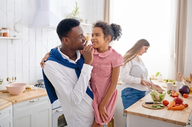 Szczęśliwa rodzina, smaczne śniadanie w kuchni. matka, ojciec i córka gotują rano, dobra relacja