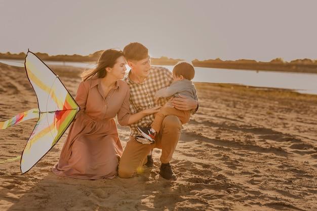 Szczęśliwa rodzina spaceru na piaszczystej plaży rzeki. ojciec, matka trzyma na rękach synka i bawi się latawcem.