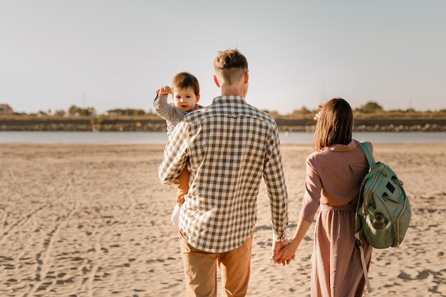 Szczęśliwa rodzina spaceru na piaszczystej plaży