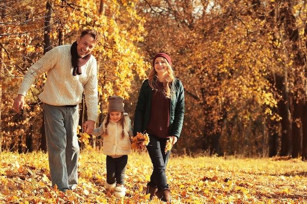 Szczęśliwa rodzina spaceru w pięknym jesiennym parku