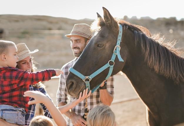 Szczęśliwa rodzina spędza dzień na świeżym powietrzu na stadninie koni - rodzice i dzieci z koniem - zwierzęca miłość