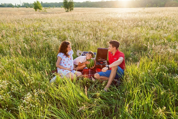 Szczęśliwa rodzina spędza razem czas na łonie natury. siedzą na kocu na polu w słoneczny letni dzień. rodzinna sesja zdjęciowa w ciąży na łonie natury