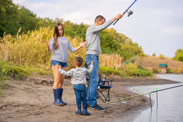 Szczęśliwa rodzina spędza razem czas; uczą syna, aby łowić ryby.