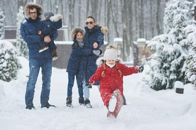 Szczęśliwa rodzina spędza zimę na świeżym powietrzu w pobliżu domu