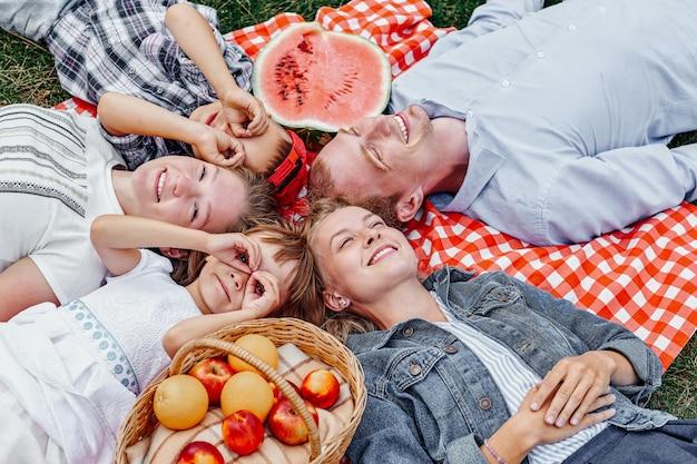 Szczęśliwa rodzina spoczywa na piknik. ciesząc się i leżąc na kraciastej kracie na łące. dorośli i dzieci patrzą w niebo