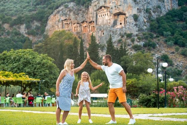 Szczęśliwa rodzina stoi na tle góry w mieście dalyan.ludzie w pobliżu grobowców licyjskich w turcji.