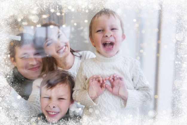 Szczęśliwa rodzina stoi za zaśnieżonym oknem, śmieje się, dzieci grymasują, pokazują języki.