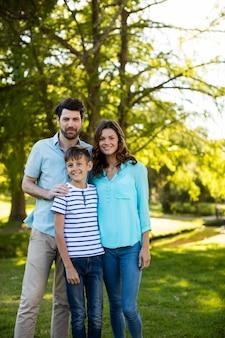 Szczęśliwa rodzina stojąc w parku