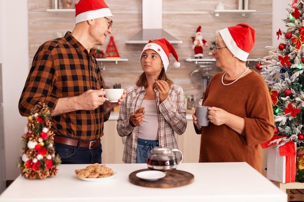 Szczęśliwa rodzina świętująca święta bożego narodzenia razem w boże narodzenie udekorowanej kuchni kulinarnej
