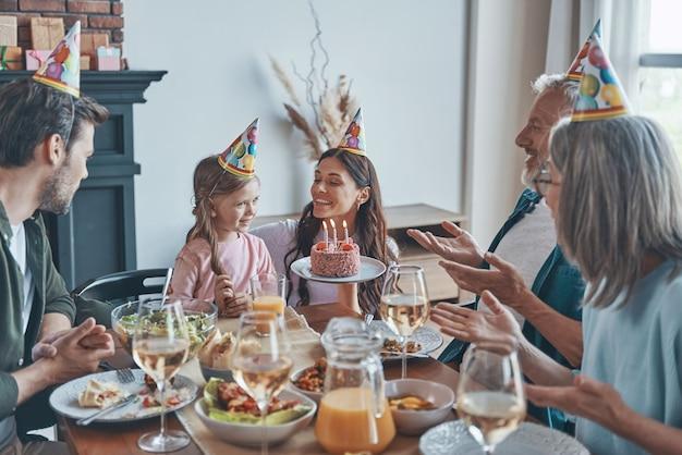 Szczęśliwa rodzina świętująca urodziny małej dziewczynki siedząc przy stole w domu