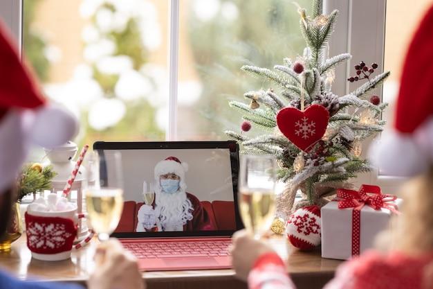 Szczęśliwa rodzina świętuje boże narodzenie online przez czat wideo w kwarantannie. koncepcja lockdown zostaje w domu. impreza bożonarodzeniowa podczas pandemii koronawirusa covid 19
