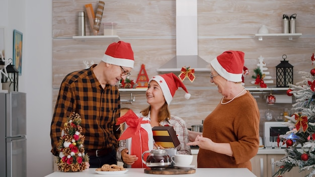 Szczęśliwa rodzina świętuje sezon zimowy ciesząc się świątecznymi świętami stojąc przy stole