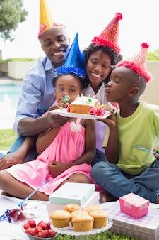 Szczęśliwa rodzina świętuje urodziny wpólnie w ogródzie