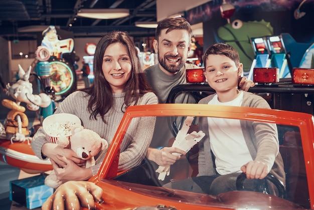 Szczęśliwa rodzina, syna obsiadanie na zabawkarskim samochodzie.