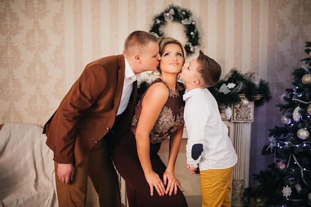Szczęśliwa rodzina tata i syn całują mamę