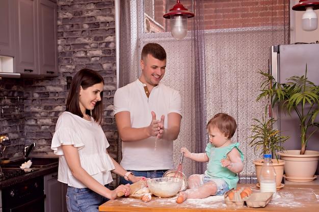 Szczęśliwa rodzina, tata, mama i córka bawią się i gotują w kuchni, zagniatają ciasto i piec ciastka