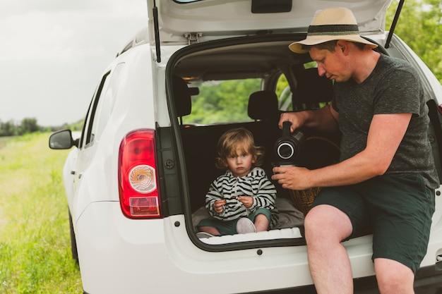 Szczęśliwa rodzina taty i syna jedzie samochodem i zatrzymała się na poboczu, żeby napić się herbaty z termosu.