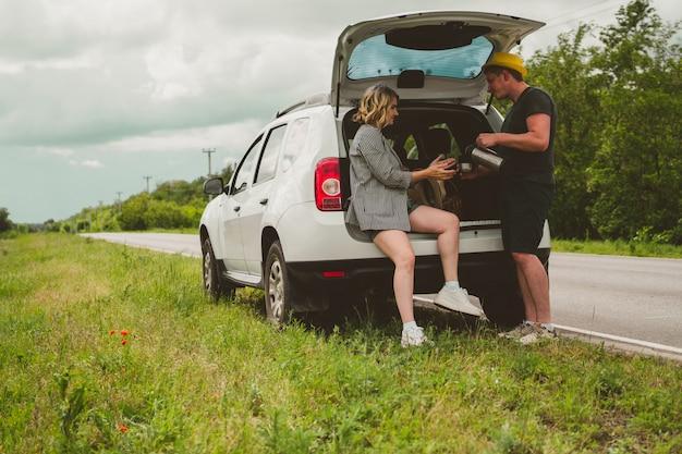 Szczęśliwa rodzina taty, mamy i syna jedzie samochodem i zatrzymała się na poboczu, żeby napić się herbaty z termosu.