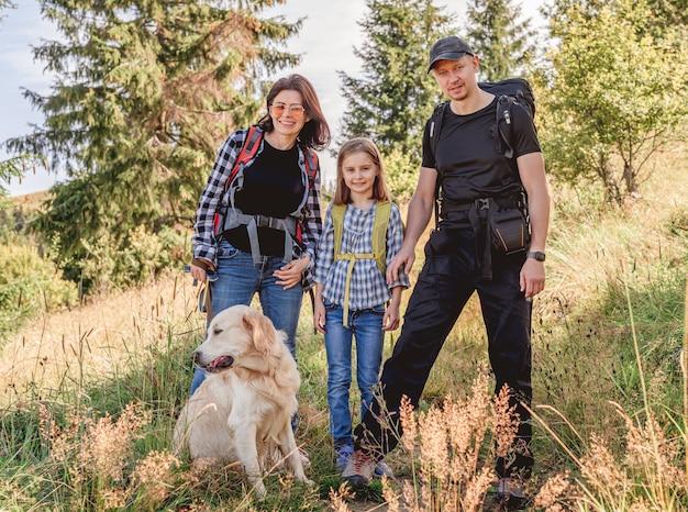 Szczęśliwa rodzina trekking w słonecznych górach z psem latem