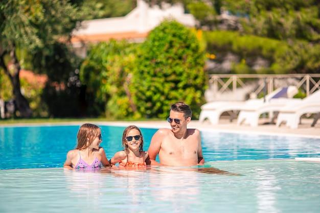 Szczęśliwa rodzina trzech osób w odkrytym basenie