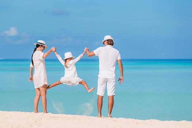 Szczęśliwa rodzina trzech zabawy razem na plaży