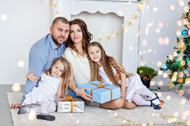 Szczęśliwa rodzina trzyma pudełka z prezentami przed białym kominkiem z elegancką choinką