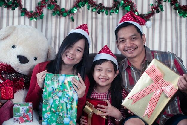 Szczęśliwa rodzina trzyma pudełko boże narodzenie prezent