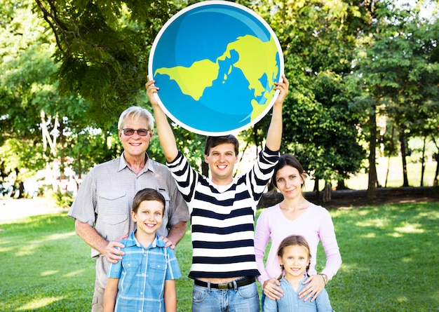 Szczęśliwa rodzina trzyma w górę kuli ziemskiej