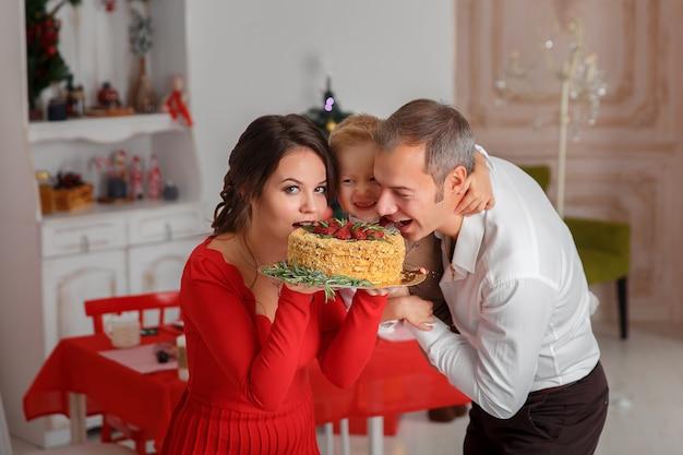 Szczęśliwa rodzina ugryźć smaczny tort na tle kuchni. święto nowego roku i zabawa.