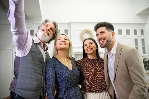 Szczęśliwa rodzina uśmiechnięci rodzice i młode małżeństwo robiące selfie na smartfonie dziadka
