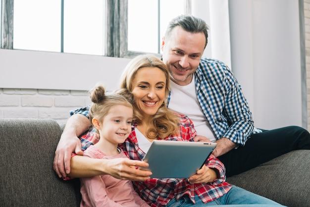 Szczęśliwa rodzina używa cyfrową pastylkę na kanapie w żywym pokoju