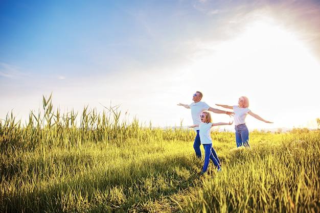 Szczęśliwa rodzina w białych koszulkach, okularach przeciwsłonecznych i dżinsach w parku