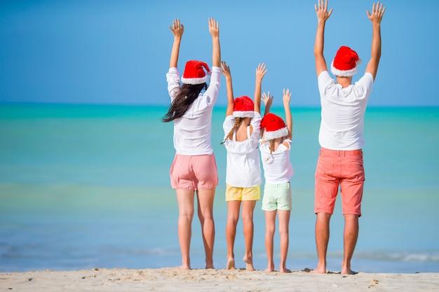 Szczęśliwa rodzina w czerwonych czapkach świętego mikołaja na tropikalnej plaży z okazji świąt bożego narodzenia